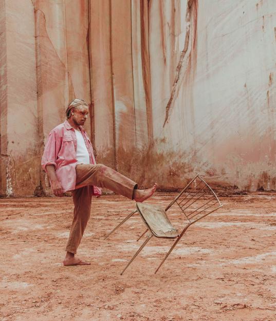 homme chaise rose marbre pousser donner un coup de pied